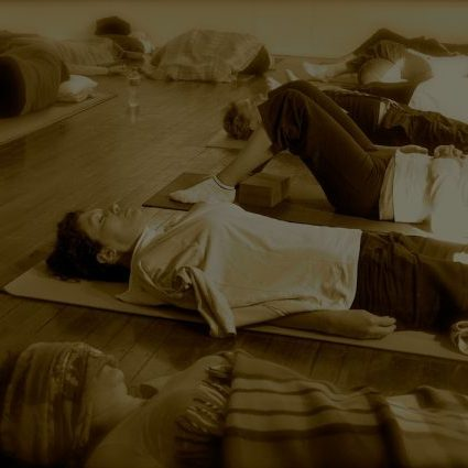 Yogis in Savasana in a yoga studio to depict the peaceful end to a Yoga class.