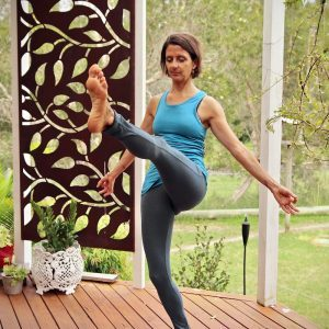 Woman balancing on one leg demonstrating a Yoga pose where the lifted leg is straight out the front.